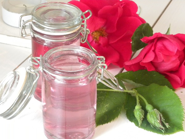 Rosenvatten på små glasflaskor med rosor i bakgrunden