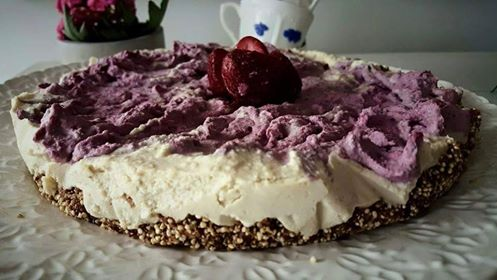 Rawfood halloncheesecake på ett vitt fat, dekorerad med jordgubbar
