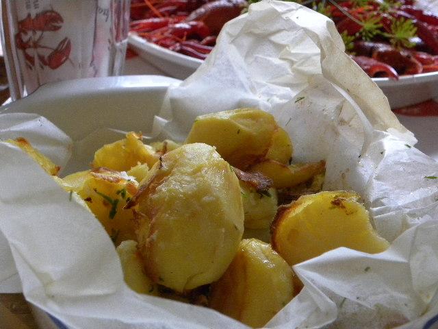 Ugnsbakad potatis i ett bakplåtspapper och kräftor i bakgrunden