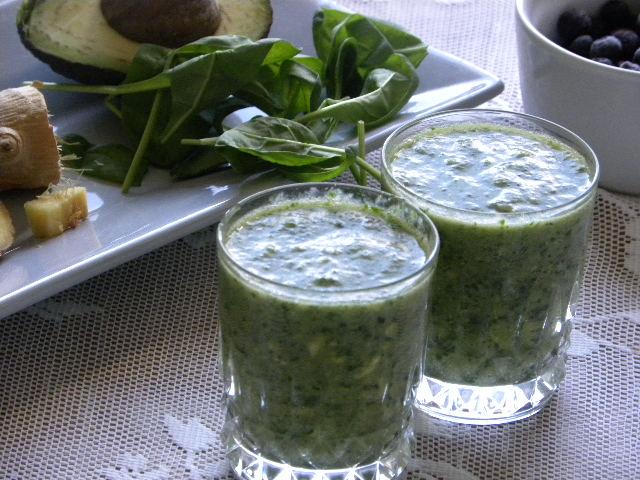 Två glas med grön smoothie. I bakgrunden ett grått fat med spenat, avokado och ingefära