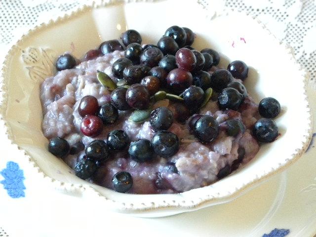 Blåbärsgröt toppad med blåbär och frön i en vit, djup tallrik