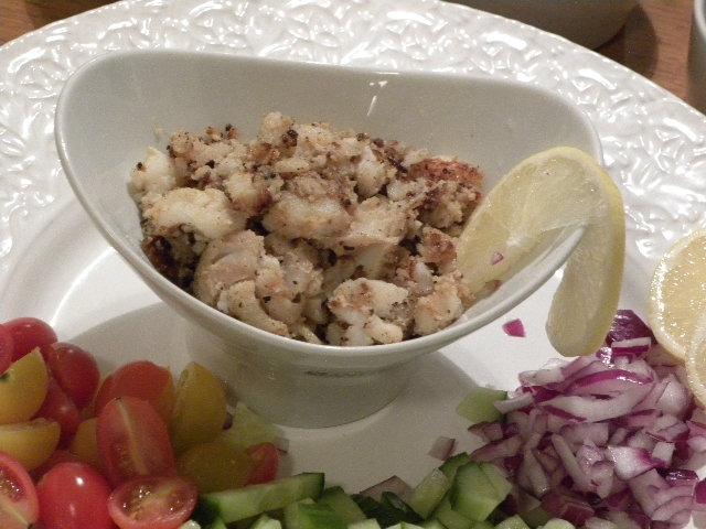 Mandelpanerad torsk i bitar i en vit skål omgiven av hackade grönsaker
