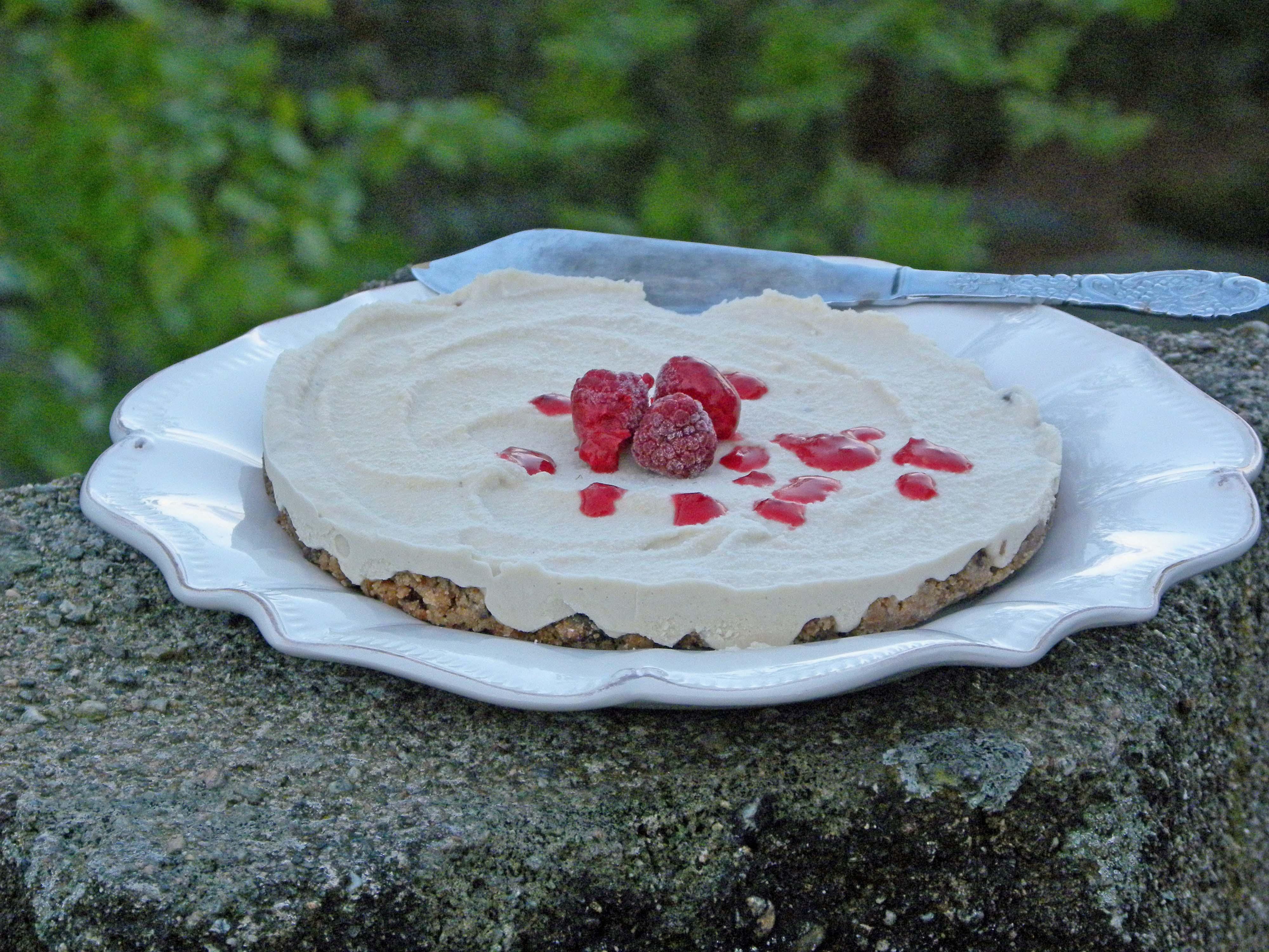 Cheesecake rawfood på ett vitt fat som står på en stenpelare