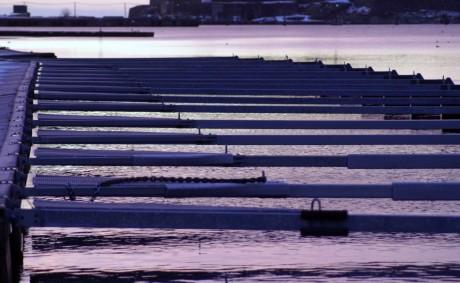En hamn på kvällskvisten, inga båtar är fästa.