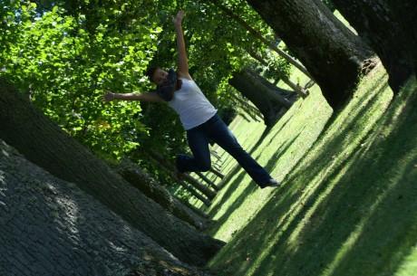 Jag (Mona) som hoppar ute i vitt linne och jeans bland gräset och träden.