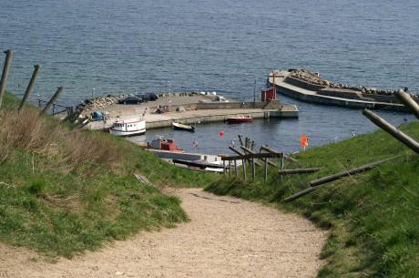 En stig fram till en hamn med ett fåtal båtar.