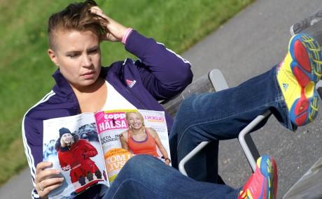 Mona som sitter i en stol med gymnastikskor och läser en tidning om hälsa.