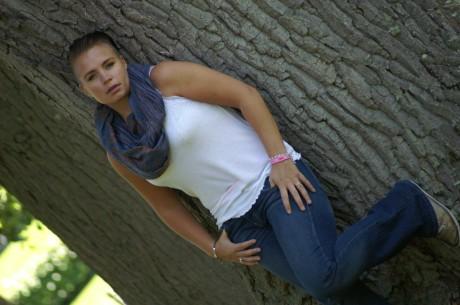 Jag (Mona) står med vitt linne, jeans och en blå scarf lutad mot ett träd.