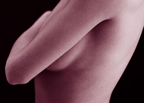 Närbild på kvinna i profil som håller armen över sina bröst
