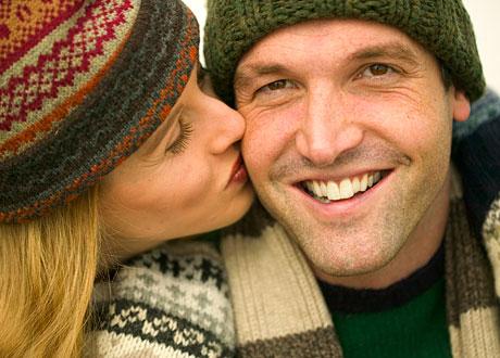 Kvinna som kysser glad man på kinden