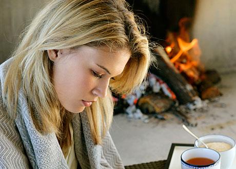 Trött ung blond kvinna tittar neråt brasa och kopp te i bakgrunden