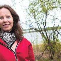 Leende Marita i röd jacka vid sjö