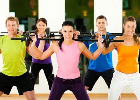 Människor grupptränar med skivstång i träningssal