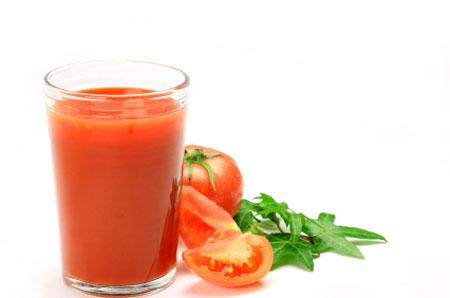 Ett glas tomatjuice och skivade tomater bredvid