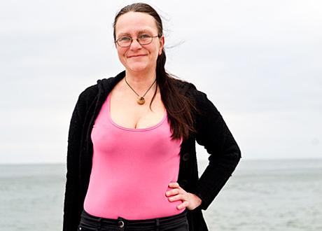 Veronica i rosa tröja på stranden.