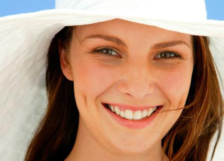 Glad kvinna i solhatt