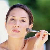 Mörkhårig kvinna med vacker hy drar med penselborste över kinden