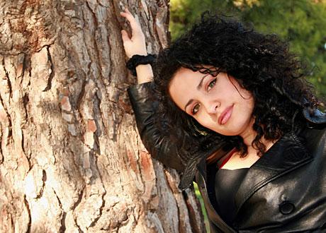 Mörkhårig söt lockig tjej lutar sig mot träd