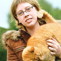 Susanne med sin katt mot grönskande utomhusbakgrund