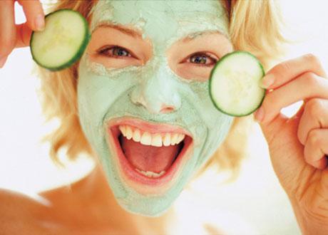 Glad kvinna med grön ansiktsmask och gurkskivor nästan framför ögonen