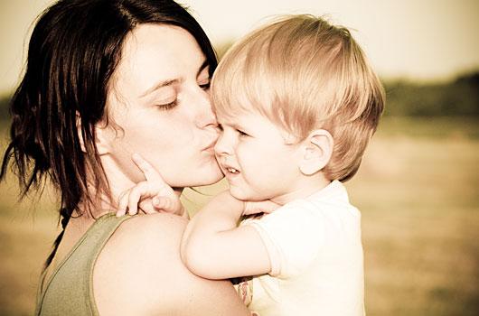 Mörkhårig kvinna pussar sin tvååring på kinden, håller honom i famnen