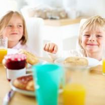 Två glada barn sitter och äter vid matbord