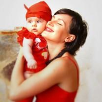 Mörkhårig kvinna i röd topp håller sin bebis kind mot kind