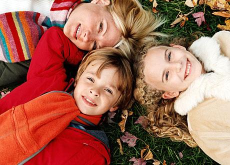Mamma och hennes två barn ligger på gräsmatta