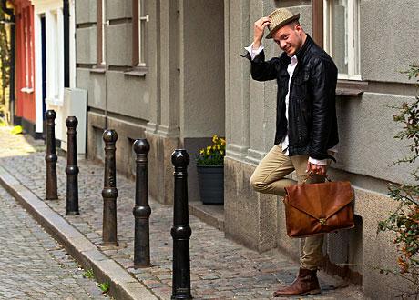 Erik Ståhl med hatt och väska lutad mot vägg utomhus