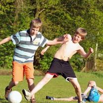 Fotbollsspelande ungdomar på gräsplan