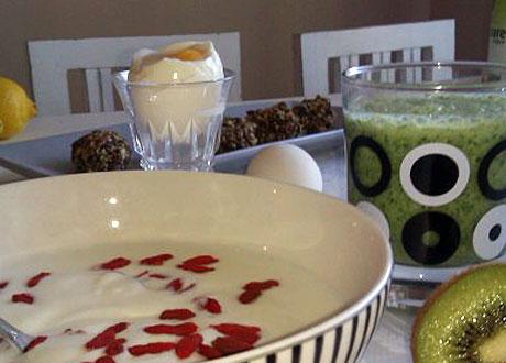 Avocadosmoothie i glas på frukostbord bredvid tallrik fil med gojjibär löskokt och ägg i glaskopp
