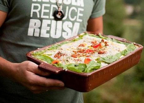 Man håller vackert upplagt rawfood-lasagne i brun ugnsfast form