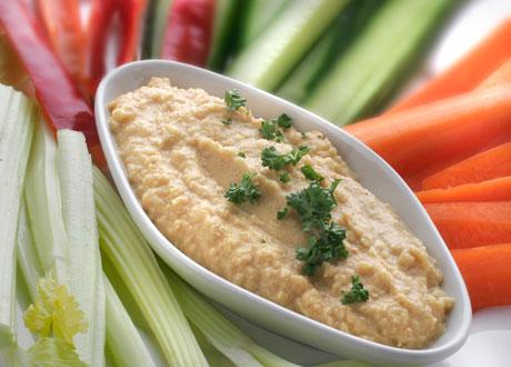Hummus i vit skål omringad av uppskurna bitar röd paprika morot gurka selleri