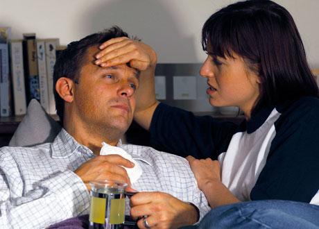 Mörkhårig ung kvinna håller pannan på jämnårig sjuk man i sängen med tekopp i handen