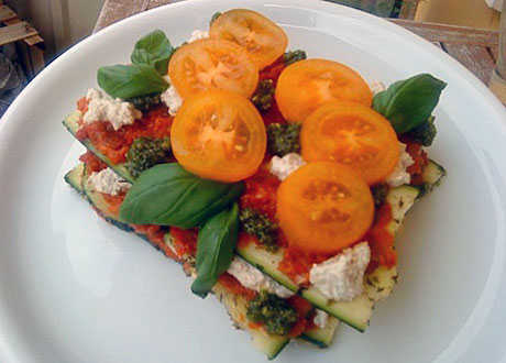 Rawfood lasagne i olika lager mellan skuren zucchini på vitt fat. Garnering gula tomater och basilika