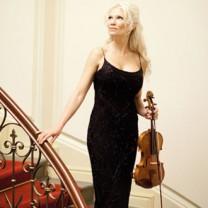 Linda Lampenius bärandes svart aftonklänning med violin i ena handen och andra handen på räcket i en vacker röd trappa