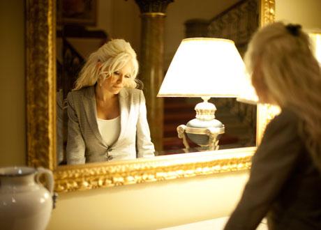 Man ser Linda Lampenius i en spegel och hon tittar neråt på ett lite melankoliskt sätt