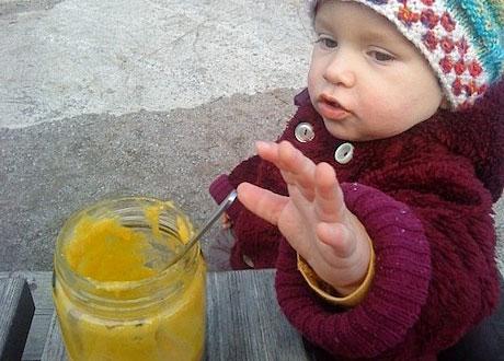 Rawfoodbaby sträcker sig hungrigt efter glasburk med gul mangogröt