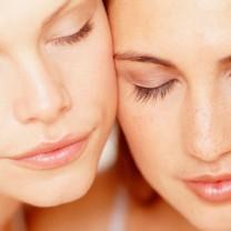 Två kvinnor med vacker ren naturlig hy sitter kind mot kind och blundar