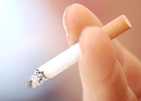 Hand håller tänd cigarett