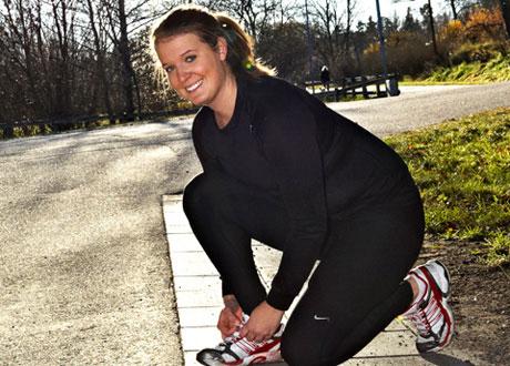 Leende Rebecca knyter gympadojjorna på en solig landsväg