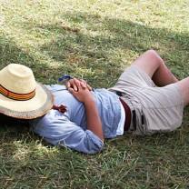 Man ligger och sover på gräsmatta med stråhatt på huvud och cigarettfimp bredvid sig