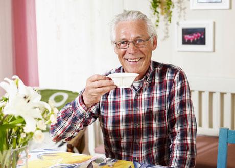 En vithårig och stilig Henry i röd-vit-blå-rutig skjorta sitter i sitt kök och dricker te