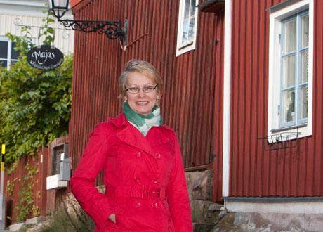 Ekaterina i röd jacka grönvit scarf utanför gammal rött hus med vita knutar