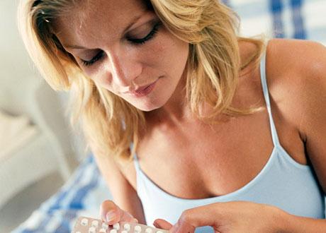 Blond unga kvinna i blått linne sitter med tablettkarta