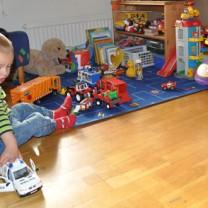 Liten pojke sitter och leker med en polisbil i sitt lekrum fullt av leksaker i olika material