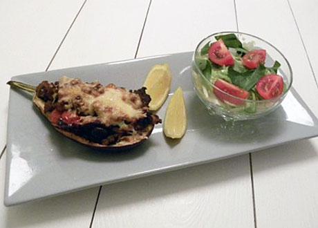 Kött- och grönsaksfylld aubergine på vitt fat med citronklyfter och liten grönsallad med tomat