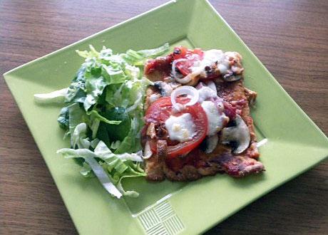Glutenfri LCHF-pizza serverad på grön tallrik med liten grönsallad