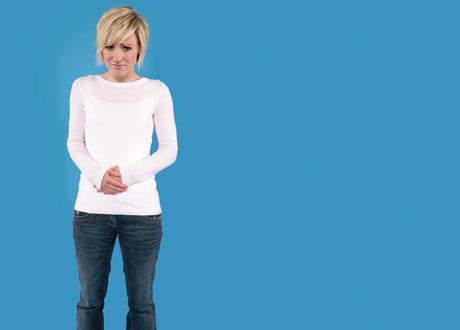 Blond ung tjej håller sig för magen och gör min av obehag