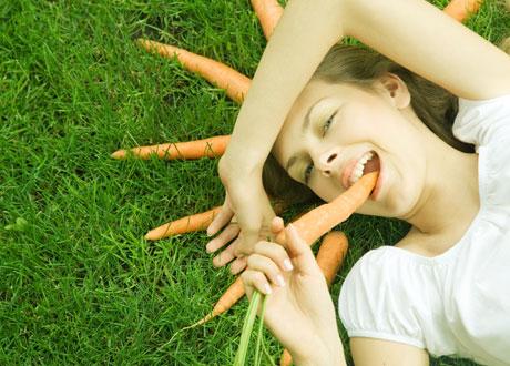Ung kvinna på gräsmatta med morot i mun och fler morötter i halvcirkel runt sitt huvud